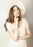 Den härliga flickan i den bredbrättade hatten som poserar och, uttrycker olika sinnesrörelser dreaminess royaltyfri foto
