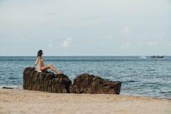 Den härliga flickan i en baddräkt som poserar på, vaggar i havet mot bakgrunden av havet arkivfoton