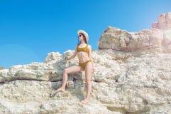 Den härliga flickan i en bikini, en hatt och en solglasögon som solbadar på bakgrunden av vit, vaggar Royaltyfri Foto