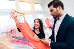 Den härliga flickan i en klänning och en attraktiv man i dräkt shoppar De är i en ljus visningslokal royaltyfri bild
