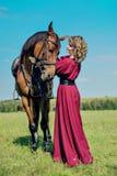 Den härliga flickan i en lång röd klänning står bredvid den bruna hästen arkivfoto