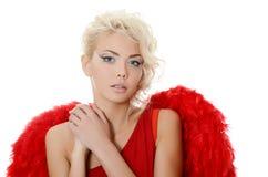 Den härliga flickan i en passa av en röd ängel Royaltyfri Bild