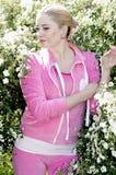 Den härliga flickan i en rosa dräkt bland den blomstra busken Arkivfoto