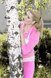 Den härliga flickan i en rosa dräkt dolde bak en björk Royaltyfri Foto