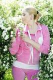 Den härliga flickan i en rosa dräkt i den blomstra busken Royaltyfria Foton