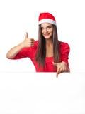 Den härliga flickan i en stor jultomten hjälpredahatt som rymmer, tömmer brädet Fotografering för Bildbyråer