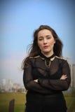 Den härliga flickan i en svart klänning på en bakgrund av staden parkerar fotografering för bildbyråer