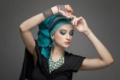 Den härliga flickan i en turban och smycken Arkivfoto