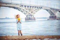 Den härliga flickan i en turkosklänning med en bukett av mimosan arkivfoton