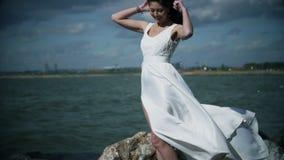 Den härliga flickan i en vit klänning står på kusten lager videofilmer