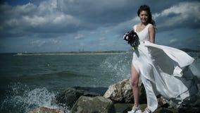 Den härliga flickan i en vit klänning står på kusten med en bukett i hennes händer Klä att fladdra i vindultrarapid stock video