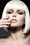 Den härliga flickan i en vit peruk, med guld- makeup och spikar Celebratory bild Härlig le flicka Royaltyfri Foto