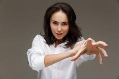 Den härliga flickan i en vit skjorta visar sinnesrörelser - le, gyckel arkivfoton