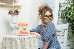 Den härliga flickan i exponeringsglas sitter på en tabell med frukt i ett ljust rum Arkivbild