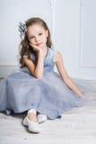 Den härliga flickan i grå färger klär, och pointeskor poserar på fet Fotografering för Bildbyråer