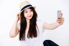 Den härliga flickan i hatten gör selfie på golvet Fotografering för Bildbyråer