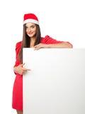Den härliga flickan i jultomten en hjälpredahatt är hållande polystyren Arkivfoto