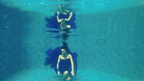 Den härliga flickan i lång blåttklänning poserar för kameran som är undervattens- i pöl stock video