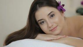 Den härliga flickan i massagemottagningsrummet ser kameran stock video