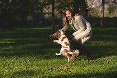 Den härliga flickan i parkera som gör lydnad, excersize med hennes stolta konung Charles Spaniel för hunden Arkivbilder