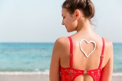 Den härliga flickan i röd baddräkt har sunblock i form av hjärta baktill på stranden royaltyfri fotografi