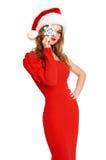 Den härliga flickan i röd kappa och den santa hatten som isoleras på vit bakgrund, jul semestrar begrepp, visar stor snöflingagar fotografering för bildbyråer