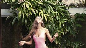 Den härliga flickan i rosa baddräkt kastar upp blommakronblad ovanför henne, ultrarapid arkivfilmer