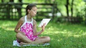 Den härliga flickan i rosa färgklänning med minnestavladatoren sitter på grönt gräs i trädgård stock video