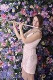 Den härliga flickan i rosa kort klänning spelar flöjten Arkivbild