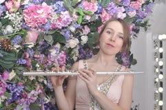Den härliga flickan i rosa kort klänning spelar flöjten Royaltyfri Fotografi