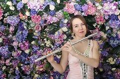 Den härliga flickan i rosa kort klänning spelar flöjten Fotografering för Bildbyråer