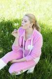 Den härliga flickan i rosa slag för en dräkt på en maskros Fotografering för Bildbyråer