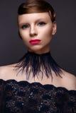 Den härliga flickan i stilen Gatsby med en krage av fjädrar och snör åt blåttklänningen Modellera med frisyren från 20-tal av 20t arkivfoto