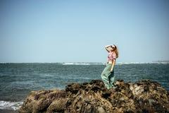 Den härliga flickan i tillfälliga kläder som kopplar av på havet, vaggar arkivfoton