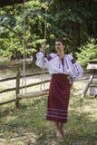 Den härliga flickan i ukrainsk nationell klänning står nära gungan Royaltyfria Foton