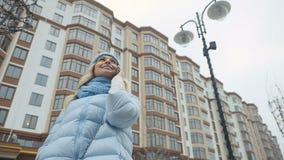 Den härliga flickan i varm kläder talar på telefonen utomhus stock video