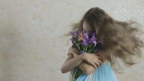 Den härliga flickan jublar den donerade buketten av blommor och virvlar runt stock video