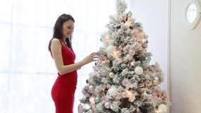 Den härliga flickan klär upp en julgran i inre stock video