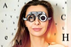 Den härliga flickan kontrollerar vision i en ögonläkare med correcti Royaltyfri Fotografi