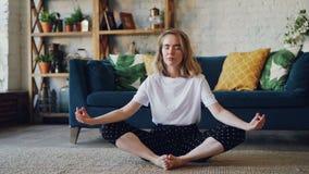 Den härliga flickan kopplar av hemma att göra yogaövningssammanträde på golv med händer på knä som stänger ögon och att andas arkivfilmer