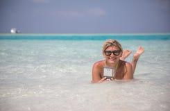 Den härliga flickan lägger i blått vatten av det indiska havet med telefonen Royaltyfria Foton