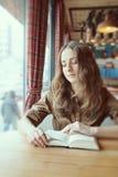 Den härliga flickan läser en bok i ett varmt kafé Arkivfoton