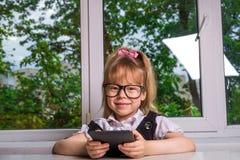 Den härliga flickan läser ett eBooksammanträde på ett skrivbord royaltyfria foton
