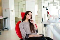 Den härliga flickan ler i den tand- stolen royaltyfri foto