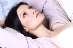 Den härliga flickan ligger på en soffa i linnen fotografering för bildbyråer