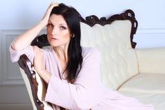 Den härliga flickan ligger på en soffa i linnen royaltyfria bilder
