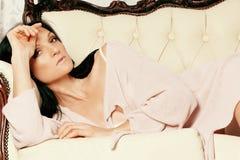 Den härliga flickan ligger på en soffa i linnen royaltyfri foto