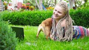 Den härliga flickan ligger på gräset och spelar med hunden HD stock video