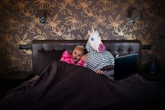 Den härliga flickan ligger på sängen med den roliga pojkvännen i festlig maskering royaltyfri foto