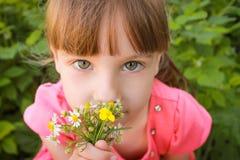 Den härliga flickan luktar blommorna arkivbilder